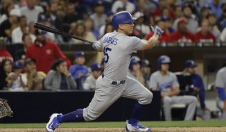 Los Angeles Dodgers' Austin Barnes watches his three-run home run during the sixth inning of the team's baseball game against the San Diego Padres on Friday, June 30, 2017, in San Diego. (AP Photo/Gregory Bull)