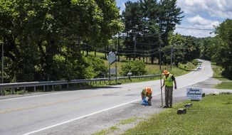 In this Tuesday, June 20, 2017 photo, Randy Reagan and his wife Kate, of New Stanton, Pa., clean up trash on the side of Old Route 119 (Center Ave), from Bruster's Ice Cream to the old Sony plant, in New Stanton, Pa. (Dan Speicher/Pittsburgh Tribune-Review via AP)