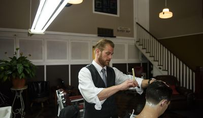 ADVANCE TUESDAY, JULY 4 - In this June 22, 2017, owner of Sandhills Shave, Mark Joas, uses a straight razor to shave Chris Arthur after a cut and style in Fayetteville, N.C. The shop keeps in use several antique items from the client chairs to the shaving cream dispensers. (Melissa Sue Gerrits/The Fayetteville Observer via AP)