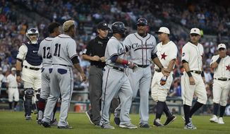Cleveland Indians first base coach Sandy Alomar Jr., center right, gets between Carlos Santana, center, and Detroit Tigers second baseman Ian Kinsler, second from right, after Santana was hit by a pitch during the fifth inning in the second baseball game of a doubleheader in Detroit, Saturday, July 1, 2017. (AP Photo/Rick Osentoski)