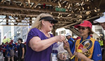 Donna Sorensen of the Waunakee, Wisconsin Lions Club trades pins with members of Taiwan's Lions Club during the Lions International street parade in Chicago celebrating the organization's 100th anniversary on July 1, 2017. (Max Herman/Chicago Sun-Times via AP)