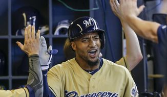 Milwaukee Brewers' Domingo Santana is greeted in the dugout after hitting a two-run home run off of Miami Marlins' Tom Koehler during the second inning of a baseball game Saturday, July 1, 2017, in Milwaukee. (AP Photo/Tom Lynn)