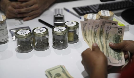 A person buys marijuana at the Essence cannabis dispensary, Saturday, July 1, 2017, in Las Vegas. (AP Photo/John Locher)