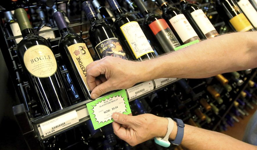 A worker at a state liquor store changes prices on wine, liquor and higher-alcohol beer, after closing to the public Friday, June 30, 2017, near downtown Salt Lake City. Higher liquor prices and other changes under a broad new Utah liquor law will take effect Saturday, along with a highway funding bill and a test program allowing people convicted of drunken driving to avoid having their driver's license suspended. (AP Photo/Rick Bowmer) ** FILE **