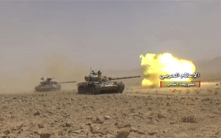 "This frame grab from video released on May 24, 2017 and provided by the government-controlled Syrian Central Military Media, shows a Syrian forces tank fires at Islamic states positions at Palmyra desert, in Homs provence, Syria. Arabic reads, ""Central Military Media, Palmyra, Syria."" (Syrian Central Military Media, via AP)"