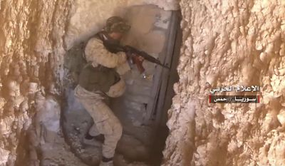 """This frame grab from video released on May 26, 2017 and provided by the government-controlled Syrian Central Military Media, shows a Syrian army soldier inspects a tunnel used by Islamic states, in Homs provence, Syria. Arabic reads, """"Central Military Media, Homs, Syria."""" (Syrian Central Military Media, via AP)"""