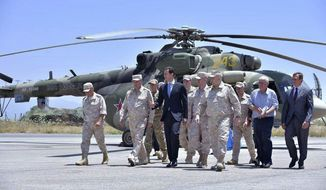 FILE -- In this June 27, 2017 file photo and released on the official Facebook page of the Syrian Presidency, Syrian President Bashar Assad inspects the Russian Hmeimim air base in the province of Latakia, Syria. (Syrian Presidency via AP, File)