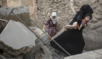 Civilians flee through a destroyed alley as Iraqi Special Forces continue their advance against Islamic State militants in the Old City of Mosul, Iraq, Sunday, July 2, 2017. (AP Photo/Felipe Dana)