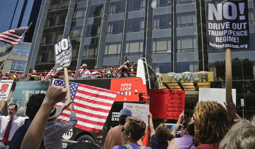 "Protesters rally outside a Trump hotel to call for the impeachment of President Trump, Sunday July 2, 2017, in New York. A statement from the organizer's website said President Trump ""has been in blatant violation of the Constitution"" and that the House of Representatives has the power to impeach him. (AP Photo/Bebeto Matthews)"