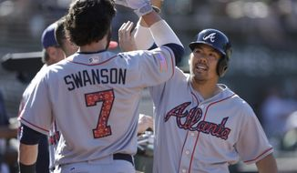 Atlanta Braves' Kurt Suzuki, right, celebrates with Dansby Swanson (7) after hitting a home run off Oakland Athletics' John Axford in the twelfth inning of a baseball game, Sunday, July 2, 2017, in Oakland, Calif. (AP Photo/Ben Margot)