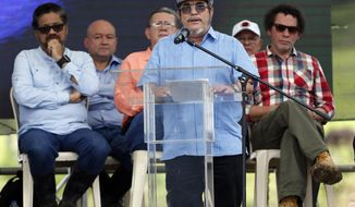 FILE - In this June, 27, 2017 file photo, Rodrigo Londono, also known as Timoleon Jimenez or Timochenko, the top commander of the Revolutionary Armed Forces of Colombia, FARC, gives his speech during an act to commemorate the completion of the disarmament process of FARC rebels, in Buenavista, Colombia. On Sunday, July 2, 2017, Timochenko was hospitalized with stroke, and remains in intensive care in Colombia. (AP Photo/Fernando Vergara, File)