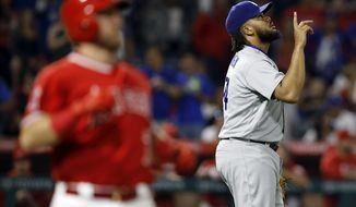 Los Angeles Dodgers relief pitcher Kenley Jansen, right, points to the sky after striking out Los Angeles Angels' Cliff Pennington, right, during the ninth inning of a baseball game in Anaheim, Calif., Thursday, June 29, 2017. The Dodgers won 6-2. (AP Photo/Alex Gallardo)