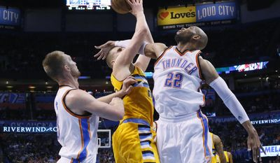 FILE - In a Wednesday, April 12, 2017 file photo, Denver Nuggets forward Nikola Jokic, center, reaches for a rebound with Oklahoma City Thunder forwards Taj Gibson (22) and Domantas Sabonis, left, during the second quarter of an NBA basketball game in Oklahoma City. Denver won 111-105. A person with knowledge of the negotiations says Sunday, July 2, 2017, that Gibson is reuniting with coach Tom Thibodeau, agreeing on a two-year, $28 million deal to join the Minnesota Timberwolves.  (AP Photo/Sue Ogrocki, File)