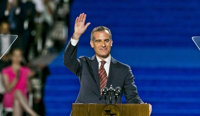 Los Angeles Mayor Eric Garcetti salutes as he is sworn in for his second term at Los Angeles City Hall Saturday, July 1, 2017. Garcetti said Los Angeles will take the lead on policies involving the environment, immigration and economic growth during a time when the nation's leaders shrink from progressive values such as freedom, leadership, bold plans and accomplishments.  (AP Photo/Damian Dovarganes)