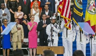 Los Angeles Mayor Eric Garcetti, front center, with his wife, Amy Elaine Wakeland, third from left, salutes the flag before being sworn in for his second term along with other city officials who have been re-elected this year at Los Angeles City Hall Saturday, July 1, 2017. At left, Herb Wesson, President of the Los Angeles City Council with his wife Fabian, far left. (AP Photo/Damian Dovarganes)