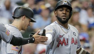 Miami Marlins' Marcell Ozuna, right, gets a hand slap after hitting a three-run home run off of Milwaukee Brewers' Junior Guerra during the third inning of a baseball game Sunday, July 2, 2017, in Milwaukee. (AP Photo/Tom Lynn)