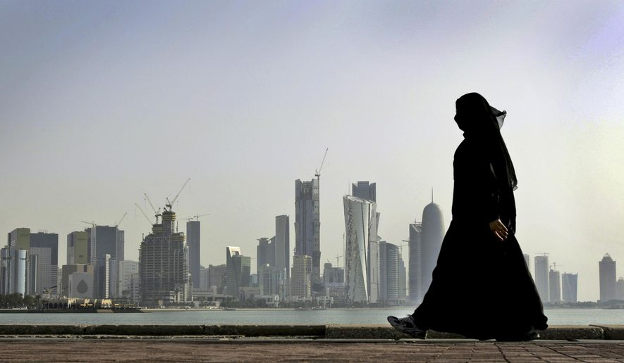 FILE- In this May 14, 2010 file photo, a Qatari woman walks in front of the city skyline in Doha, Qatar. Qatar likely faces a deadline this weekend to comply with a list of demands issued to it by Arab nations that have cut diplomatic ties to the energy-rich country, though its leaders already have dismissed the ultimatum. (AP Photo/Kamran Jebreili, File)