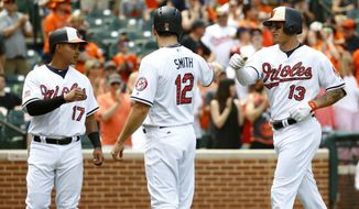 Baltimore Orioles' Manny Machado, right, greets teammates Ruben Tejada, left, and Seth Smith at home plate after batting them in on a three-run home run in the third inning of a baseball game against the Tampa Bay Rays in Baltimore, Sunday, July 2, 2017. (AP Photo/Patrick Semansky)