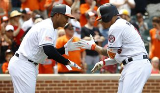 Baltimore Orioles' Jonathan Schoop, left, greets teammate Manny Machado after Machado hit a three-run home run in the third inning of a baseball game against the Tampa Bay Rays in Baltimore, Sunday, July 2, 2017. (AP Photo/Patrick Semansky)
