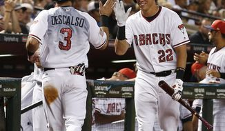Arizona Diamondbacks' Daniel Descalso (3) celebrates his run against the Colorado Rockies with Jake Lamb (22) during the first inning of a baseball game Saturday, July 1, 2017, in Phoenix. (AP Photo/Ross D. Franklin)