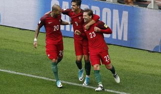Portugal's Adrien Silva, right, celebrates with teammates Ricardo Quaresma, left, and Andre Silva after scoring his side's second goal during the Confederations Cup, third place soccer match between Portugal and Mexico, at the Moscow Spartak Stadium, Sunday, July 2, 2017. (AP Photo/Alexander Zemlianichenko)