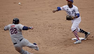Kansas City Royals' Alcides Escobar throws to first for the double play hit into by Minnesota Twins' Eduardo Escobar after forcing Miguel Sano (22) out at second during the fifth inning of a baseball game, Sunday, July 2, 2017, in Kansas City, Mo. (AP Photo/Charlie Riedel)