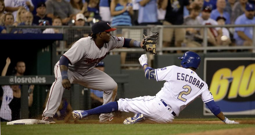 Kansas City Royals' Alcides Escobar (2) beats the tag by Minnesota Twins third baseman Miguel Sano after hitting a triple during the sixth inning of a baseball game Friday, June 30, 2017, in Kansas City, Mo. (AP Photo/Charlie Riedel)