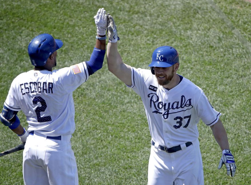 Kansas City Royals' Brandon Moss (37) celebrates with Alcides Escobar (2) after hitting a solo home run during the fifth inning of the first baseball game of a doubleheader against the Minnesota Twins Saturday, July 1, 2017, in Kansas City, Mo. (AP Photo/Charlie Riedel)