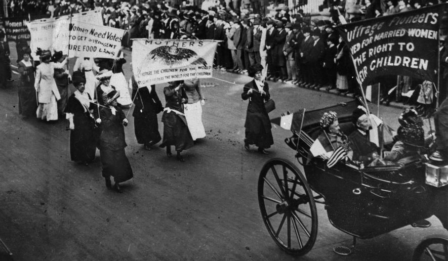 Alice Paul, in the background holding a rolled-up banner, was part of the suffragettes marching from the Women's Party headquarters to the White House in 1917. (Associated Press/File)
