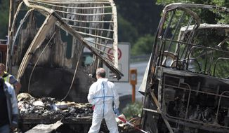 Police experts work on the burned out shell of the travel bus at the place of the accident on the motorway A9. near Muenchberg, Germany, Monday, July 3, 2017.  Several people are feared dead after a bus carrying a group of German senior citizens crashed into a truck on a highway in Bavaria early Monday and burst into flames, police said.  (Nicolas Armer/dpa via AP)