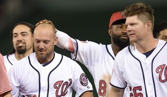 Washington Nationals' Ryan Raburn has his head rubbed by Brian Goodwin (8) after he hit a walk off single to score the winning run after a baseball game against the New York Mets, Monday, July 3, 2017, in Washington. Also seen is Nationals' Adam Lind (26). The Nationals won 3-2. (AP Photo/Nick Wass)