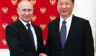 Russian President Vladimir Putin, left, and China's President Xi Jinping pose for a photo prior to their dinner in the Kremlin in Moscow, Russia, Monday, July 3, 2017. Chinese President has arrived in Russia for talks focusing on expanding cooperation with Moscow just as tensions between U.S. and China have flared up. (Sergei Chirikov/Pool Photo via AP)