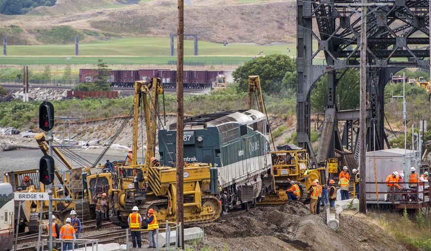 Crews put a derailed Amtrak locomotive back on the tracks Monday, July 3, 2017, in Steilacoom next to the bridge over Chambers Creek, Wash. There were only minor injuries when the locomotive and baggage car of the Amtrak Cascades train carrying 267 passengers derailed on Sunday. (Peter Haley/The News Tribune via AP)
