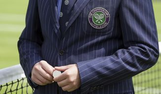 A referee prepares to toss a coin for Italy's Simone Bolelli against Taiwan's Yen-Hsun Lu on the opening day at the Wimbledon Tennis Championships in London Monday, July 3, 2017. (AP Photo/Tim Ireland)