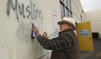 FILE - In this Feb. 1, 2017 file photo, Tom Garing cleans up racist graffiti painted on the side of a mosque in what officials are calling an apparent hate crime in Roseville, Calif. California's attorney general says the number of hate crimes increased about 11 percent last year, the second consecutive double-digit increase after years of decline. The report released Monday, July 3, 2017, shows 931 hate crimes statewide in 2016, nearly 100 more than in 2015. (AP Photo/Rich Pedroncelli, File)