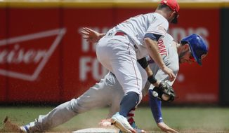 Chicago Cubs' Kris Bryant, right, is caught stealing by Cincinnati Reds shortstop Zack Cozart, center, in the fifth inning of a baseball game, Sunday, July 2, 2017, in Cincinnati. (AP Photo/John Minchillo)