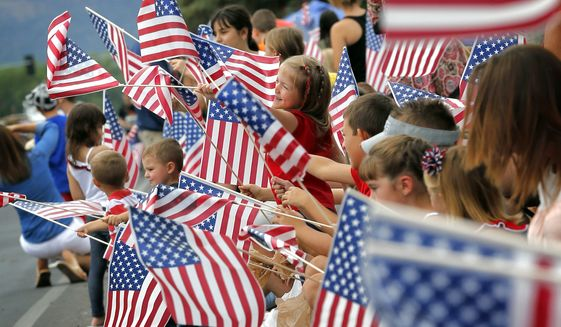 Kids, flags and a small town Independence Day parade rolls down Main Street in Eagar, Arizona. (AP Photo/Matt York)