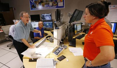FILE - In this Oct. 5, 2016, file photo, hurricane specialist branch chief James Franklin, left, talks with administrative officer Jannette Perez at the National Hurricane Center in Miami. Franklin, a retiring chief of the hurricane specialist unit at the National Hurricane Center in Miami says further cuts to tropical weather research threaten to undermine recent improvements in hurricane intensity forecasts. (AP Photo/Wilfredo Lee, File)