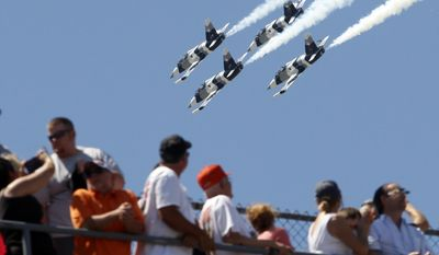 FILE - In this May 25, 2014, file photo, fans watch as four L-39 Albatros high-performance jet trainer aircraft flown by the Black Diamond Jet Team, a civilian-owned aerobatic jet team, perform a fly-over during the national anthem before the Indianapolis 500 IndyCar auto race at the Indianapolis Motor Speedway in Indianapolis. The anthem has been a standard part of U.S. sports games since World War II. Experts say Game 1 of the 1918 World Series between the Boston Red Sox and the Chicago Cubs helped pave the way. The song became the official national anthem in 1931. (AP Photo/Tom Strattman, File)