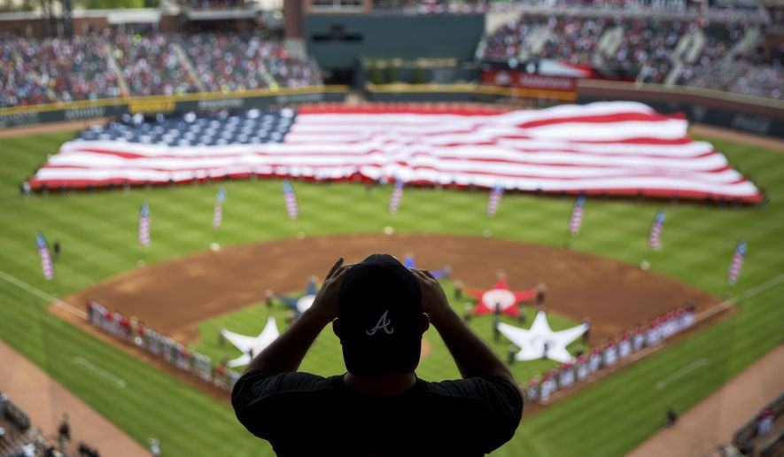 In this May 20, 2017, file photo, a spectator takes a photo of a United States flag as it is unveiled for the national anthem as part of Military Appreciation Day before a baseball game between the Atlanta Braves and the Washington Nationals in Atlanta. The anthem has been a standard part of U.S. sports games since World War II. Experts say Game 1 of the 1918 World Series between the Boston Red Sox and the Chicago Cubs helped pave the way. The song became the official national anthem in 1931. (AP Photo/David Goldman, File)