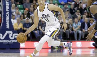 This March 1, 2017 photo shows Utah Jazz guard Dante Exum (11) bringing the ball up against the Minnesota Timberwolves during the second half of an NBA basketball game in Salt Lake City. NBA Summer League rosters are typically full of rookies getting their first taste of the league or other players young in their career trying to catch on with a roster. Exum was the No. 5 overall pick in the 2014 draft and will be running the team, again, as he tries to find a more secure place in the 2017-18 Jazz rotation. (AP Photo/Rick Bowmer)