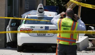 "Emergency personnel work at the scene where a taxi driver struck a group of pedestrians, injuring several, Monday, July 3, 2017, in Boston. A police official said the crash is believed to be a case of ""operator error"" in which the driver stepped on the gas pedal instead of the brake. (AP Photo/Michael Dwyer)"