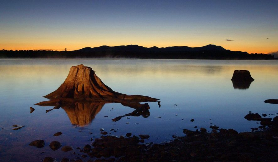 FILE - In this Sept. 5, 2001, file photo, the first light of dawn silhouettes the Katahdin Range east of Chesuncook Lake in Township 3, Range 13, Maine. (AP Photo/Robert F. Bukaty, File)