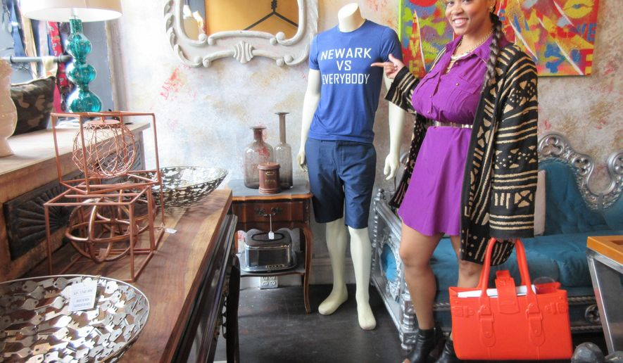 "This June 16, 2017 photo shows Lauren Craig, who calls herself the ""glambassador"" of Newark, N.J., pointing to a ""Newark Vs Everybody"" T-shirt on display at the Off the Hanger and ANE boutique on Linden Street in Newark. Craig is the author of the forthcoming travel guidebook, ""100 Things to Do in Newark Before You Die,"" and says the store, which sells fashion, art and decor, is one of her favorite local spots. Riots scarred Newark 50 years ago this summer, but tourism officials are hoping to attract more visitors as the city charts its comeback. (AP Photo/Beth J. Harpaz)"