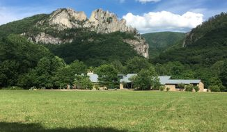 In this June 24, 2017 photo Seneca Rocks rises behind the Monongahela National Forest Discovery Center in eastern West Virginia. The crag draws serious rock climbers though guides say they also bring novices up its easier routes to the summit. (AP Photo/Michael Virtanen)
