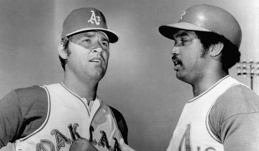Denny McClain, left, made his first appearance in an Oakland A'S uniform since coming to the team in trade for two minor leaque pitchers from the Texas Rangers March 8,1972 in Mesa, Ariz. Reggie Jackson, taking extra hitting practice, was on hand to greet him when most of the team had a day off from practice. (AP Photo)