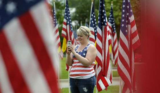 A woman takes photos at a Fourth of July display of flags Tuesday, July 4, 2017, in Merriam, Kan. (AP Photo/Charlie Riedel)