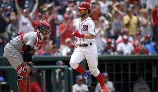 Washington Nationals' Bryce Harper, right, comes in to score on a double by Daniel Murphy as New York Mets catcher Rene Rivera, left, looks on during the eighth inning of a baseball game, Tuesday, July 4, 2017, in Washington. The Nationals won 11-4. (AP Photo/Nick Wass)