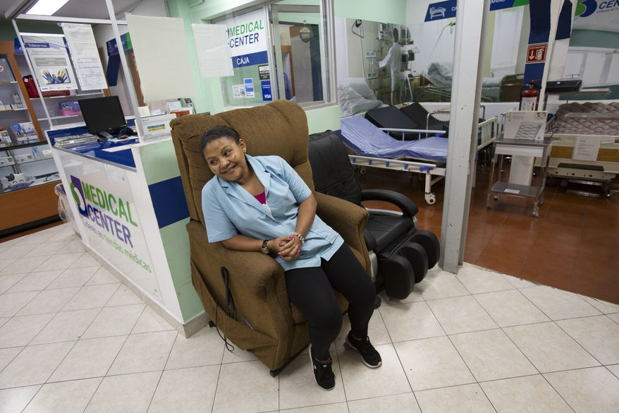 In this June 27, 2017 photo, Honduran refugee Laura Maria Cruz Martinez sits in a display chair as she waits for customers at the medical supplies store where she works in Mexico City. About five months after first applying for refugee status at Mexico's southern border, Martinez's family moved to Mexico City with the help of the United Nations refugee commission and Cruz found a job as a store clerk near downtown. (AP Photo/Rebecca Blackwell)