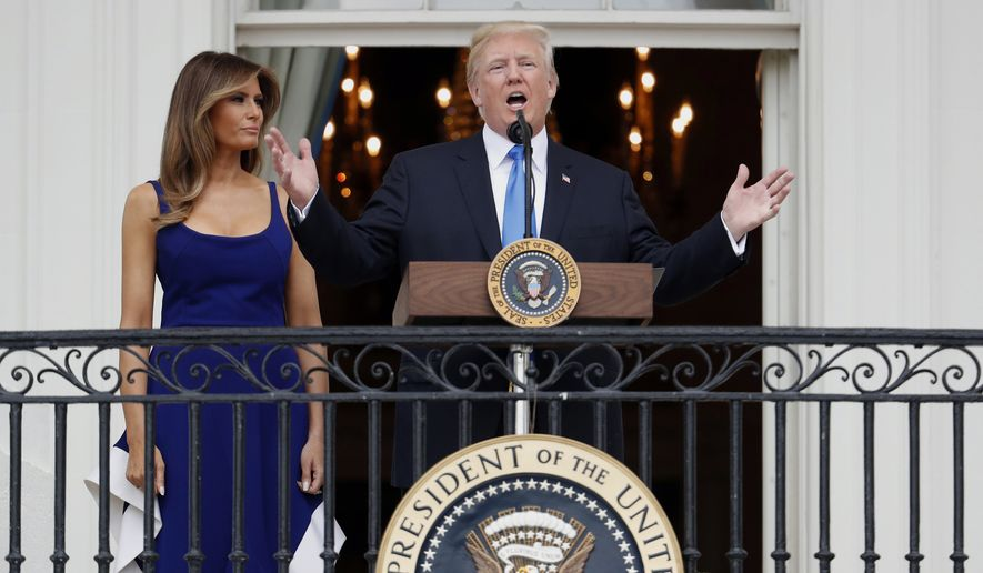 President Donald Trump, with first lady Melania Trump, speaks from the Truman Balcony at the Fourth of July picnic for military families on the South Lawn of the White House, Tuesday, July 4, 2017, in Washington. (AP Photo/Alex Brandon)